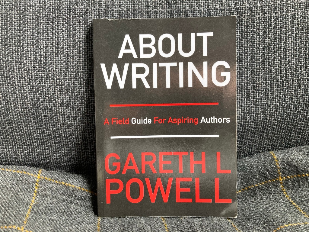 """A black book on a gray background. The book is """"About Writing: A Field Guide for Aspiring Authors"""" by Gareth L Powell. The title and name are in wwhite and red."""