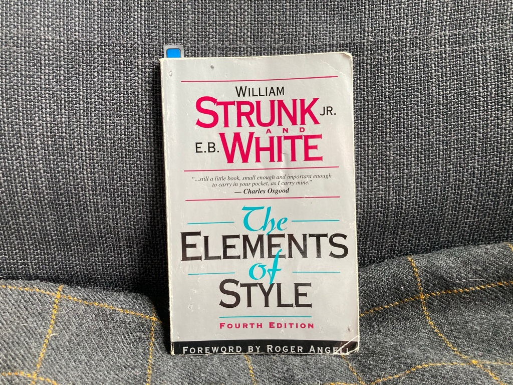 """A silver book with some red, black, and blue. The book is """"The Elements of Style: Fourth Edition"""" by William Strunk Jr. and E.B. White."""