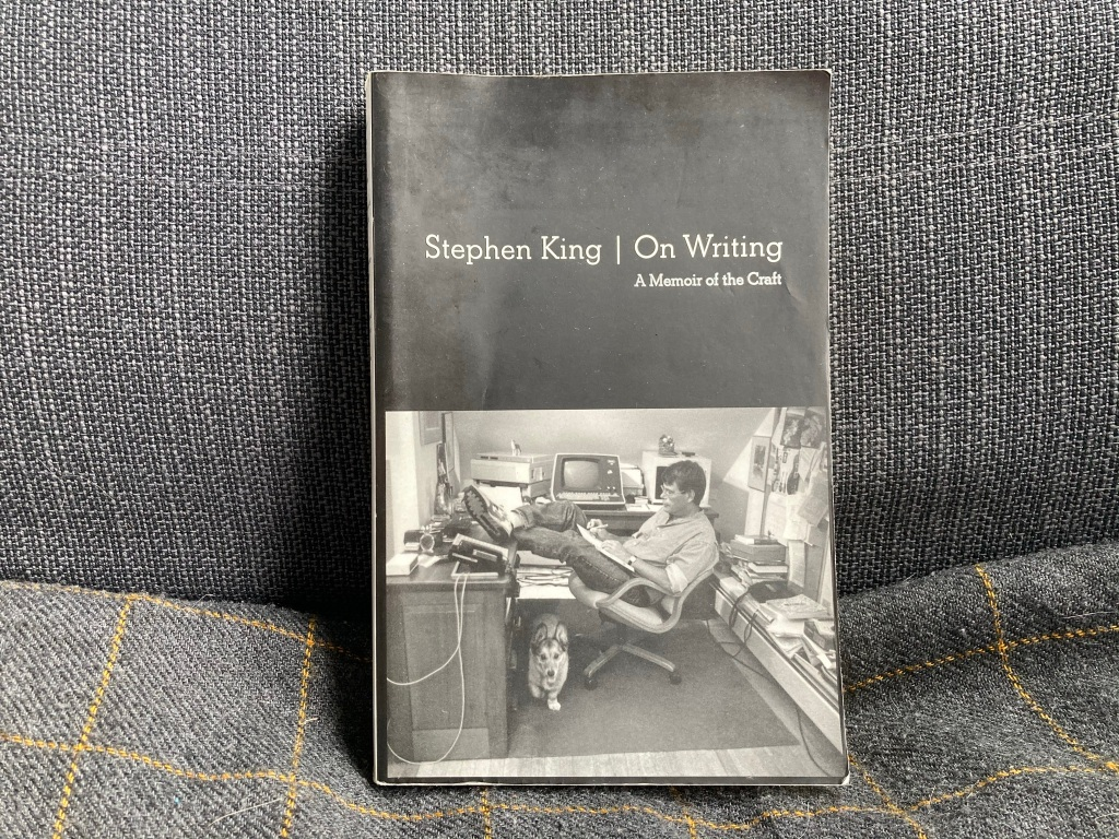 """A black and gray book on a gray background. The book is Stephen King's """"On Writing: A Memoir of the Craft."""" It has a picture of Stephen King leaning back in a chair of a small office with a corgi under his legs."""