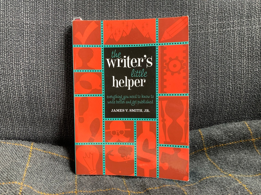 """A red, black and blue-green book on a gray background. The book is """"The Writer's Little Helper: Everything you need to know to write better and get published."""" There are some generic pictures on the book, such as a drawn mountain range and a puzzle piece."""
