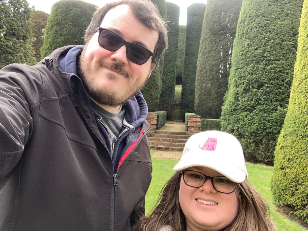 A tall, bearded man in a black jacket with glasses on the left. Beside him, there is a short woman (myself) wearing glasses and a white ball cap with a pink cat on it. In the back ground, there is a garden with large, pruned shrubs.