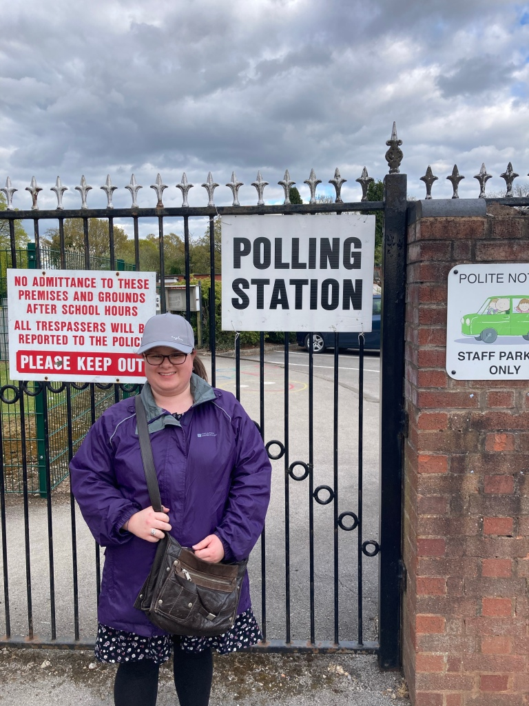 """A woman (myself) with a grey ball cap, a purple jacket, and a brown bag is standing in front of a gate. On the gate there are some generic school signs, but there is also a """"Polling Station"""" sign that I am standing beside."""